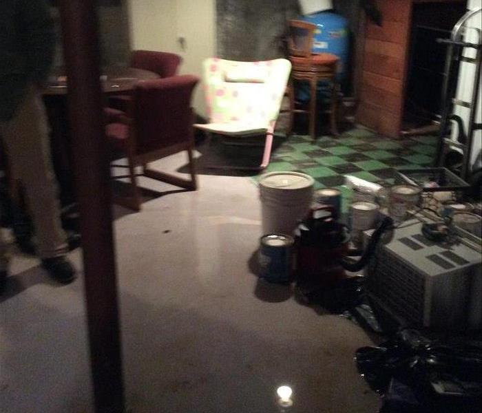 Unfinished basement round table & 2 red chairs, lawn chair, paint cans. AC, & shopvac on floor. Green & black checkered floor