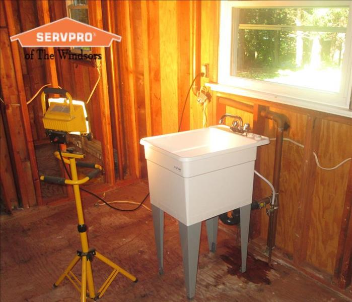 Wood Framing of a kitchen, white temporary sink in front of window SERVPRO of The Windsors Logo
