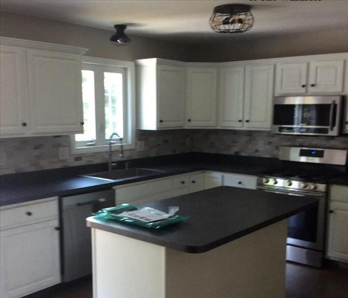 Kitchen post repair work, island and counters that are white with black counters, dark wood floors