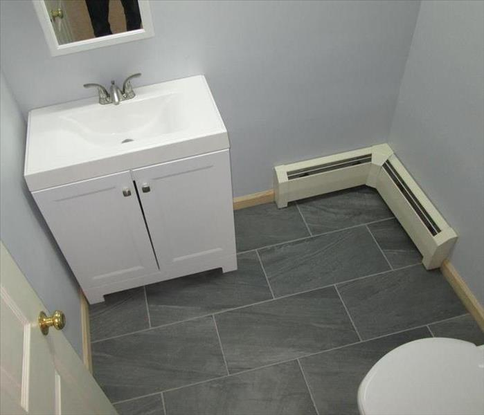 bathroom, sparkling white vanity, toilet bowl, baseboard heaters, servpro logo, gray nice floors