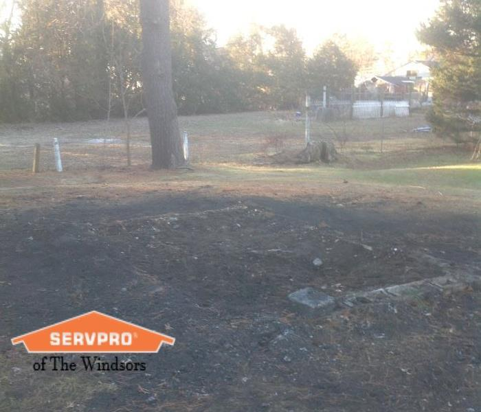 Outdoors, patch of burnt grass, trees in the back, SERVPRO of The Windsors Logo