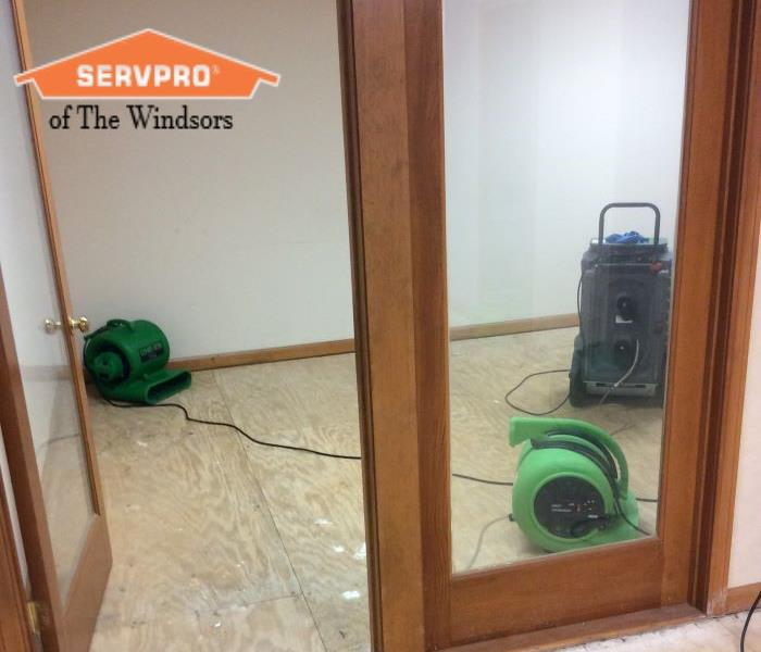 Office, double window doors, subfloor exposed, 2 green fans & 1 dehumidifier set up, SERVPRO of The Windsors Logo