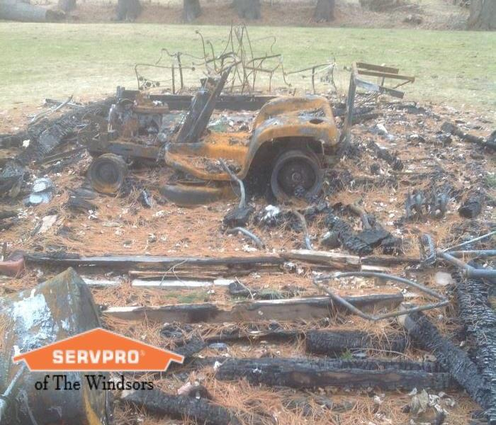Burnt remains from a shed fire, rusted race cart, burnt pieces of wood, SERVPRO of The Windsors logo