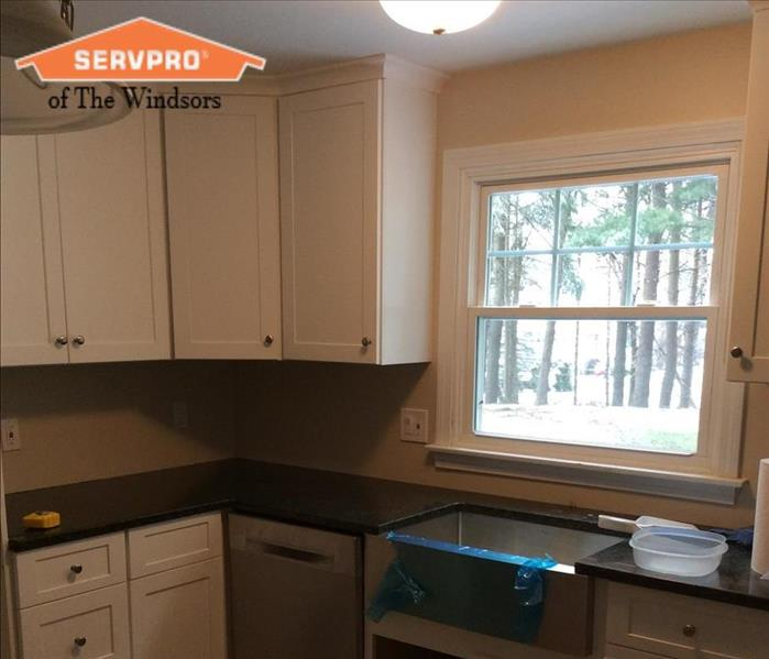 Kitchen with white cabinetry Black counter tops and Stainless steel appliances SERVPRO of The Windsors Logo