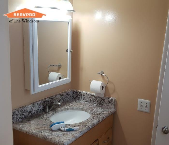 Bathroom light colored walls, light wood vanity & granite counter, white medicine cabinet SERVPRO of The Windsors Logo