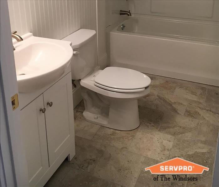 Bathroom with white vanity, walls & toilet, light vinyl floors SERVPRO of The Windsors Logo