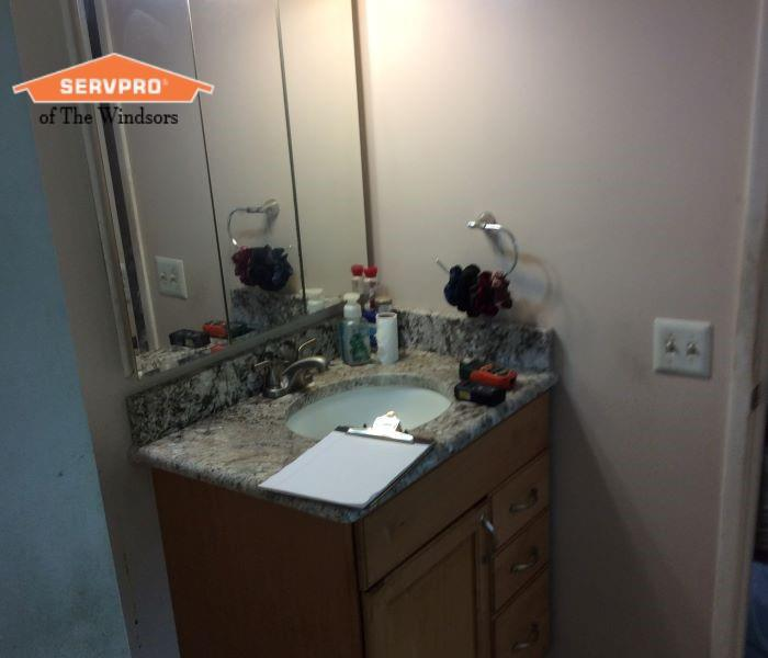 Bathroom with light colored walls, light color wood vanity with granite counter, SERVPRO of The Windsors Logo