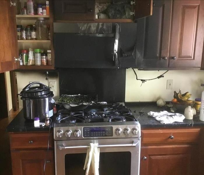 Kitchen fire, burnt cabinetry and appliances, walls covered in soot, and contents of cabinets.