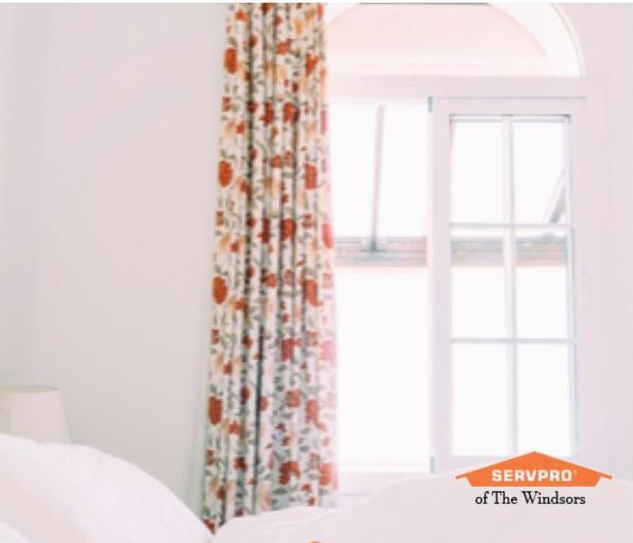 White Bedroom with white linens, Orange and white floral drapery and orange SERVPRO Logo