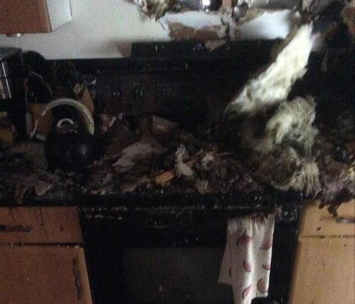 Kitchen fire, stove covered in debris, broken wall with insulation hanging out, and customers belongings destroyed by fire