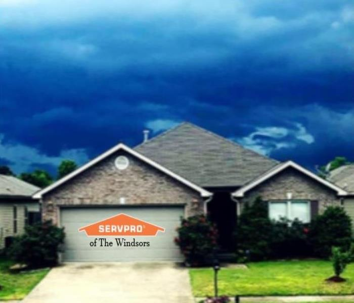 House, front lawn, sky with clouds showing impending bad weather, servpro logo.